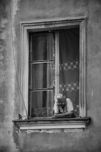 Man sitting on window of old building