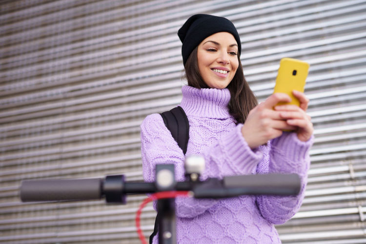 Portrait of woman photographing with mobile phone