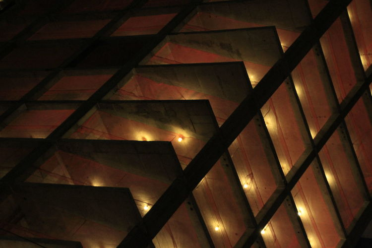 Low angle view of illuminated skylight in building
