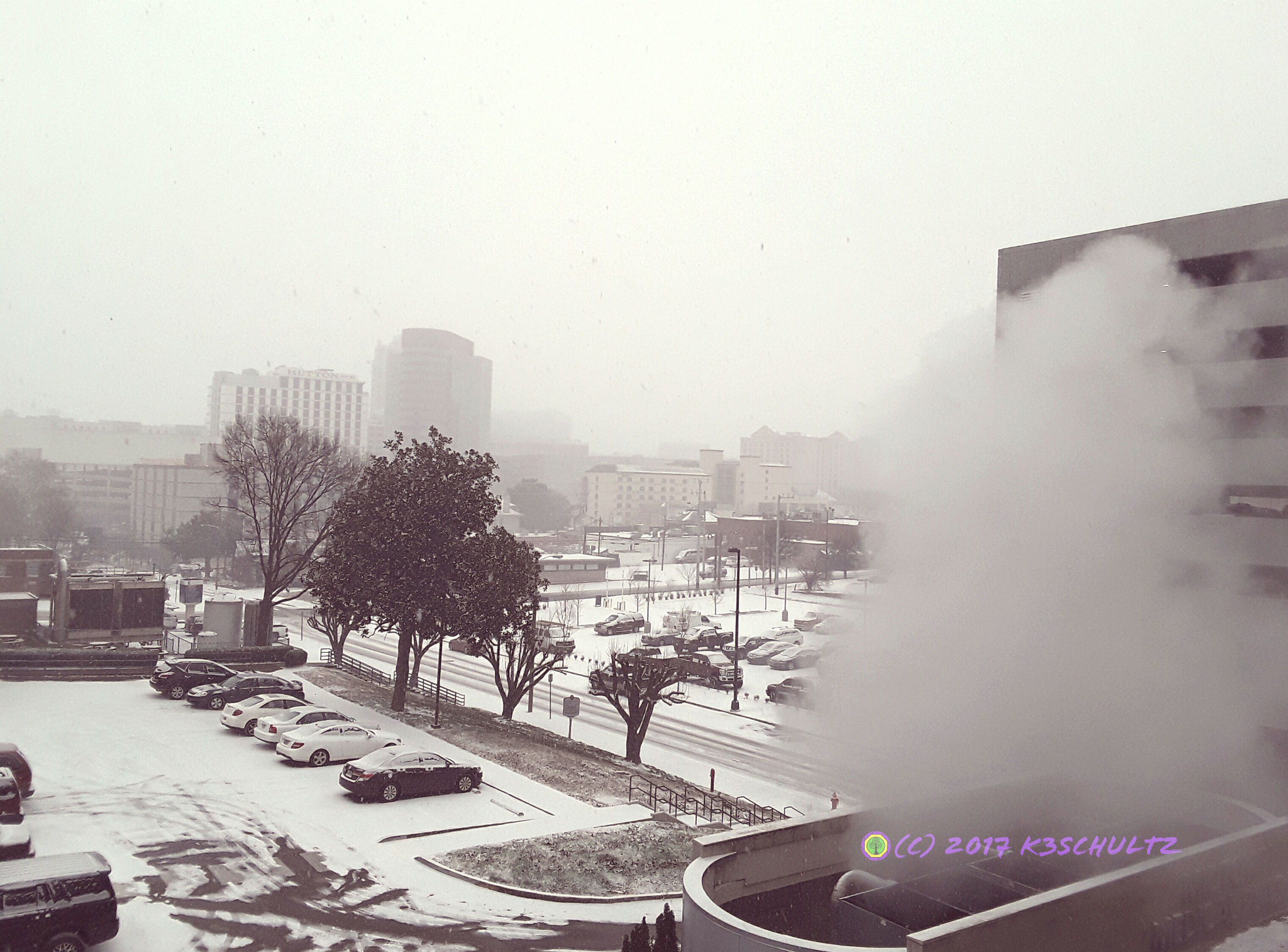 building exterior, city, architecture, built structure, transportation, fog, land vehicle, city life, urban skyline, sky, skyscraper, outdoors, day, cold temperature, cityscape, no people