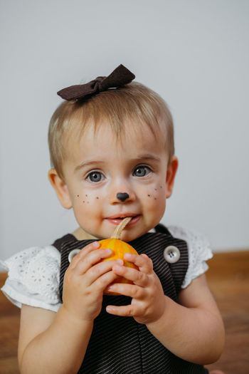 Halloween thanksgiving makeup ideas for kids and baby. happy funny baby with a pumpkin on home