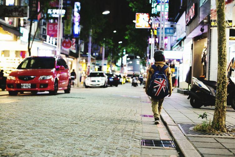 Rear View Of Boy Walking City Street At Night