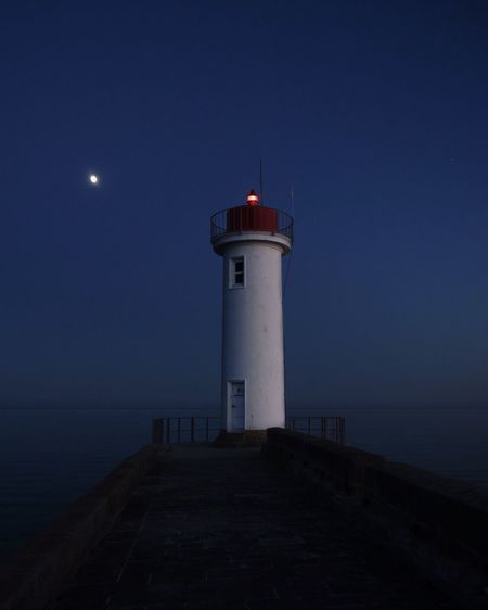 Dusk Blue Color Blue Moonlight Lighthouse Tower Built Structure Architecture Building Exterior Guidance Sky Night Direction Building Sea Water Safety Security Protection Beach Scenics - Nature Land No People