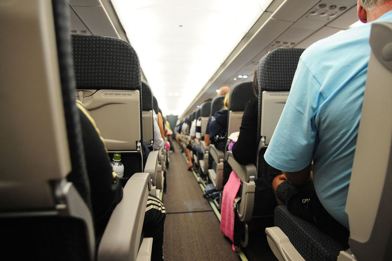 Passengers Sitting On Vehicle Seats In Airplane