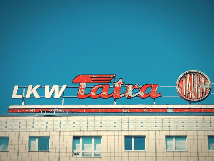 DDR Lkw Tatra Socialism Industry Reklame Mitte Berlin Berliner Ansichten Berlin Photography Tatra Lkw Tatra DDR Time Blue Red Advertising Sign City Plattenbau Architecture Building Exterior Neon Day No People Sky Outdoors Text Clear Sky Low Angle View