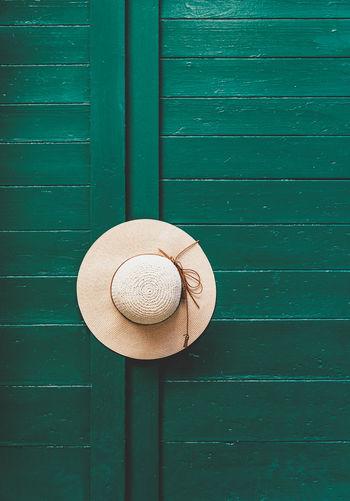 Hat on green door. minimalist, minimalism, entrance.