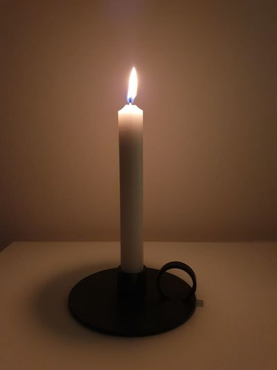 Close-up of lit candle on table in darkroom