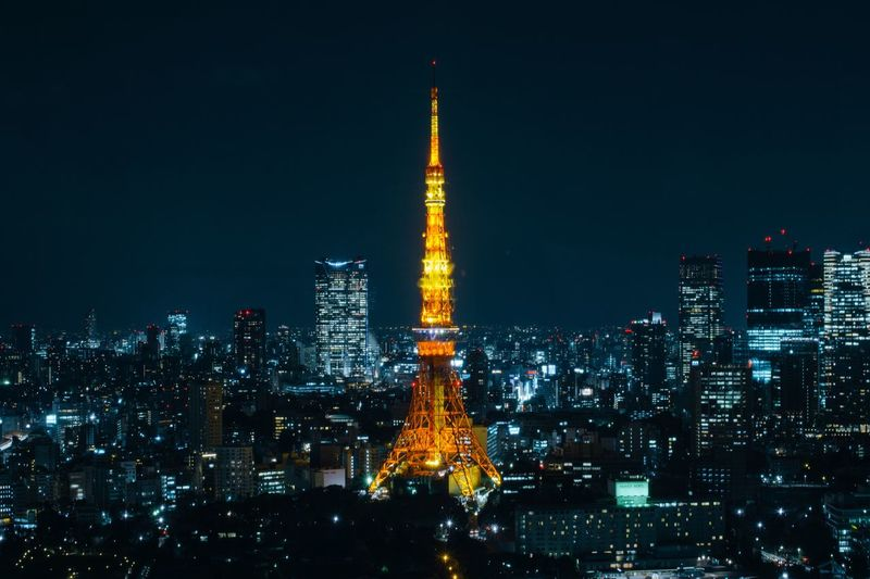 Illuminated tokyo tower amidst buildings at night