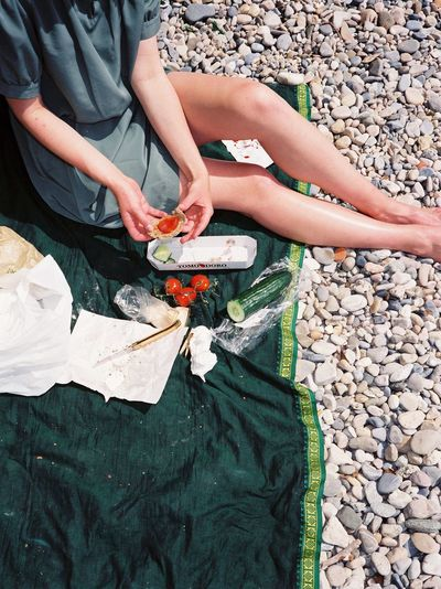Low section of woman preparing food while sitting at beach