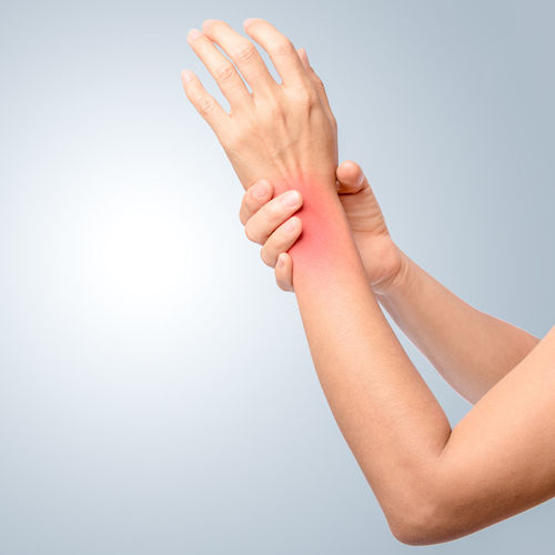 Cropped hands of woman with wrist pain over gray background