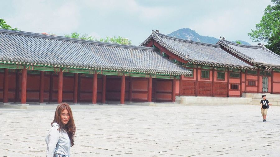 Woman standing by traditional building against sky