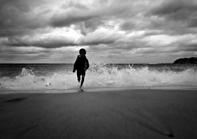 Full Length Of Boy Running On Shore At Beach Against Cloudy Sky