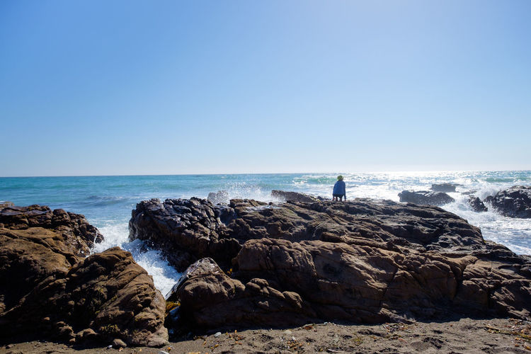 Rear view of man standing on rock by sea against clear sky