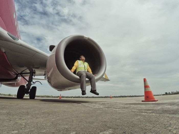 Full length of worker sitting on airplane jet engine at runway