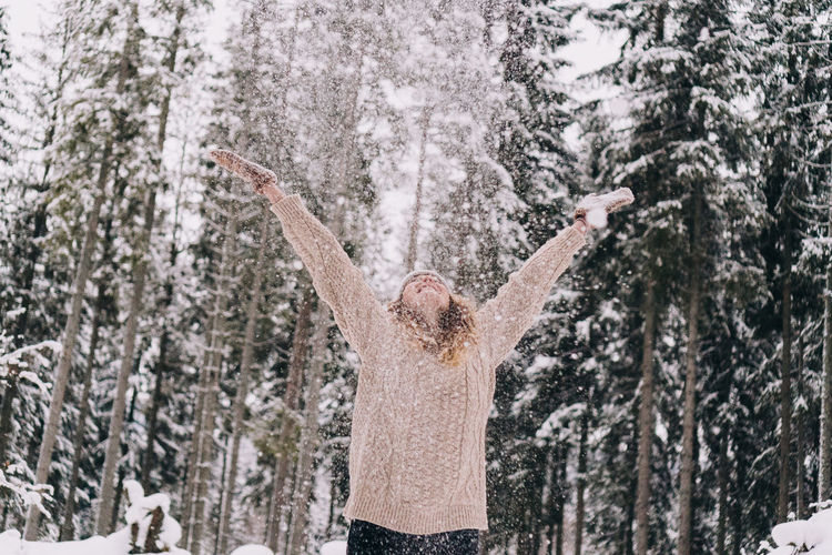 Panoramic shot of person on snow covered trees in forest