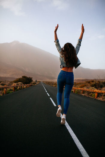 Teide National Park - Women - Tenerife Fashion Stories Happy People Holiday SPAIN Teide National Park Brunette Casual Clothing Freedom Of Expression Full Length Human Arm Leisure Activity Lifestyle Photography Lifestyles Mountain One Person Outdoors Raised Hands Real People Road Tenerife Transportation Travel Destinations Young Adult Young Women