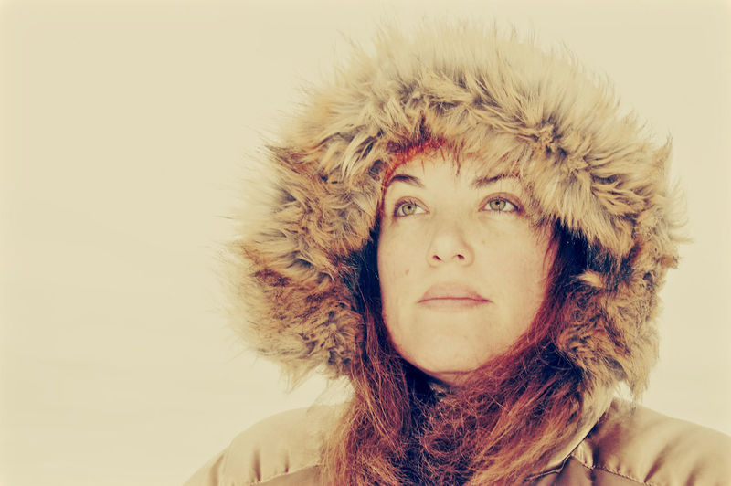 Close-up of thoughtful mature woman in warm clothing looking away against beige background