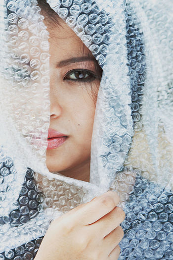 Close-Up Portrait Of Young Woman Wrapped In Bubble Wrap
