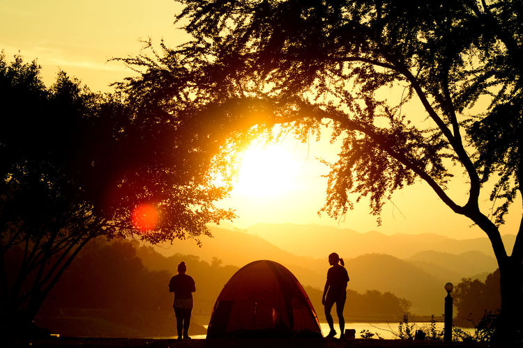 Silhouette Women Standing By Tent Against Orange Sky