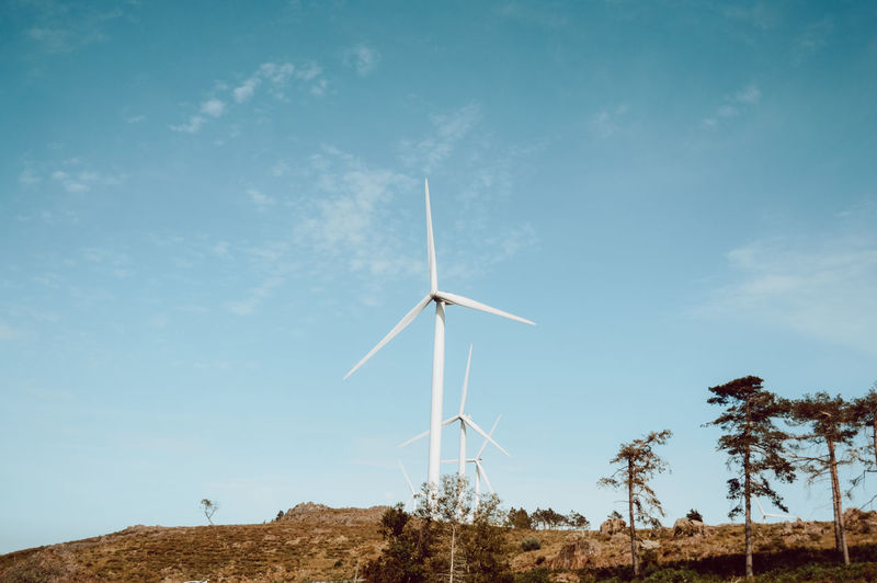 Low angle view of windmills on landscape against sky