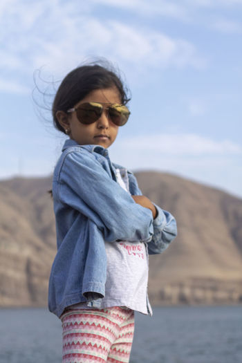 Cute little girl is watching the waves of the sea from the shores of the beach Casual Clothing Child Childhood Day Fashion Focus On Foreground Glasses Innocence Land Leisure Activity Lifestyles Nature One Person Outdoors Sea Sky Standing Sunglasses Three Quarter Length Water Wind
