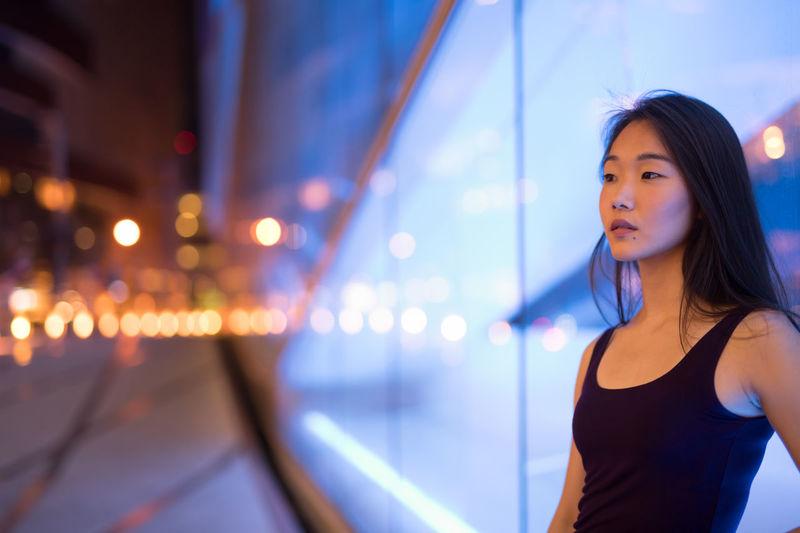 Woman looking away at illuminated city at night