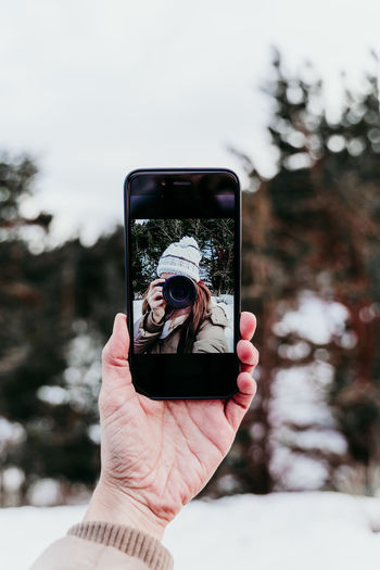 Cropped hand of woman holding smart phone while photographing outdoors during winter
