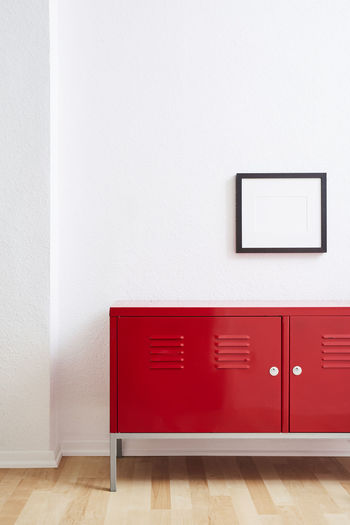 Red wooden door with white wall