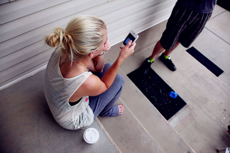 High Angle View Of Woman Using Phone On Steps By Man