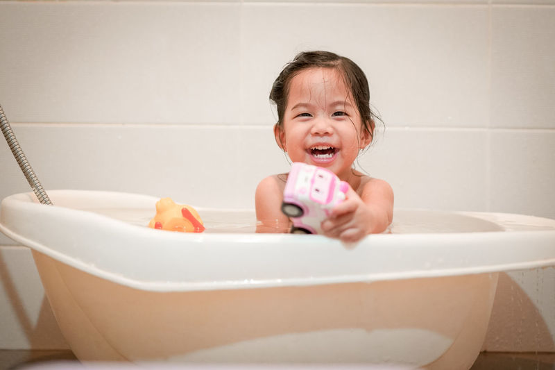 Portrait of smiling girl playing with toy in bathtub