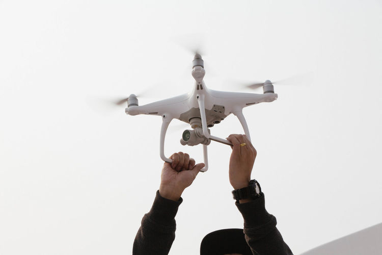 Drone  Aerospace Industry Air Vehicle Airplane Body Part Copy Space Day Flying Hand Holding Human Body Part Human Hand Human Limb Low Angle View Mode Of Transportation Motion One Person Personal Perspective Plane Real People Transportation Unrecognizable Person White Background