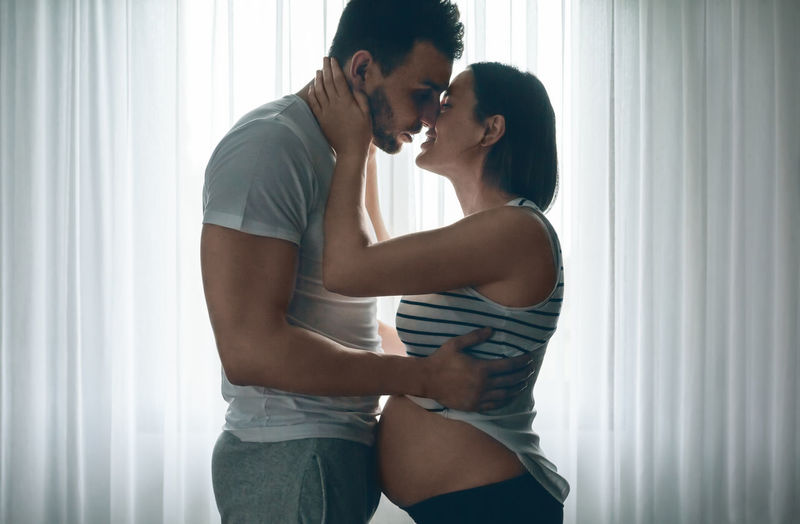Man embracing and kissing his pregnant woman Baby Care Caress Family Horizontal Love Man Maternity Mother Motherhood Wait Woman Caucasian Expectation Father Female Girl Holding Male Maternal Mom Pregnancy Pregnant Tummy Two People
