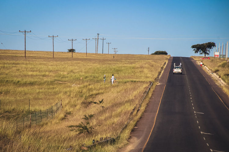 Man riding motorcycle on road amidst field against clear sky