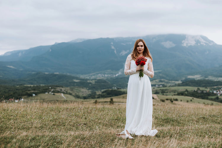 Beautiful bride in wedding dress holding red flowers outdoors