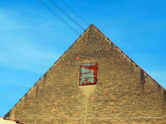 Old building Architecture Roof Nature Sky Blue Building Sunlight Wall Day Outdoors Cable Clear Sky No People Low Angle View Building Exterior Built Structure Wall - Building Feature High Section Triangle Shape Old Old Building  Door Shutter Rusty Metal