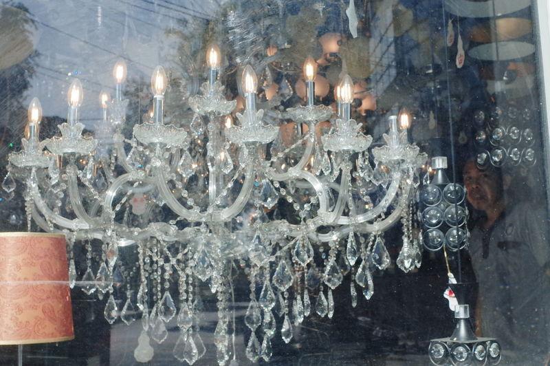 Close-up of illuminated lighting equipment hanging on glass