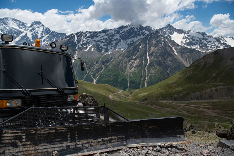 A black grader stands in the mountains in summer.  ratrak, a machine for paving roads in the snow