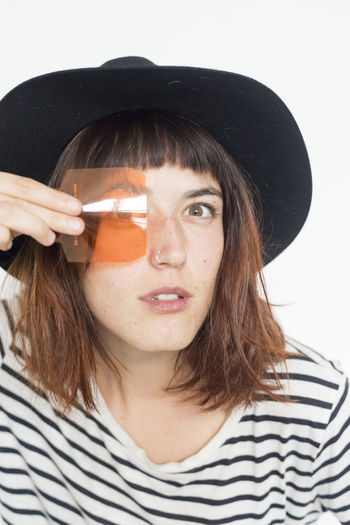 Portrait Of Young Woman Looking Through Orange Plastic Against White Background