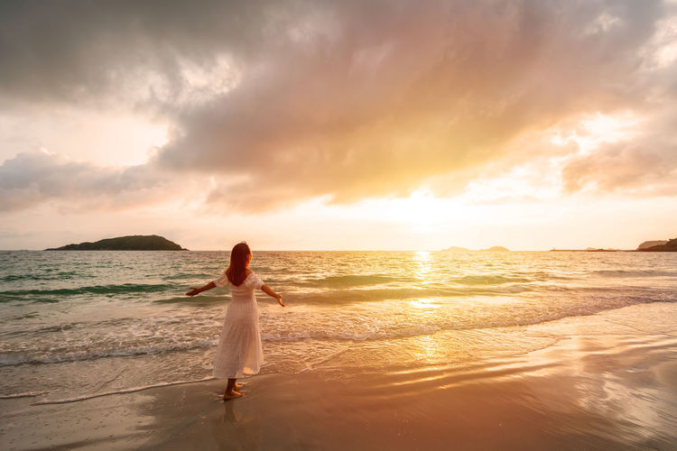 Woman on beach against sky during sunset