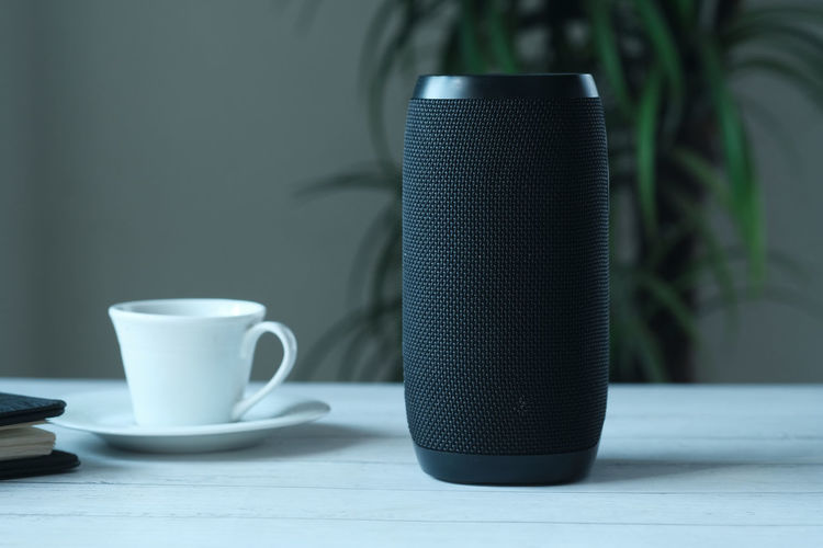 Smart speaker and tea cup on wooden table.