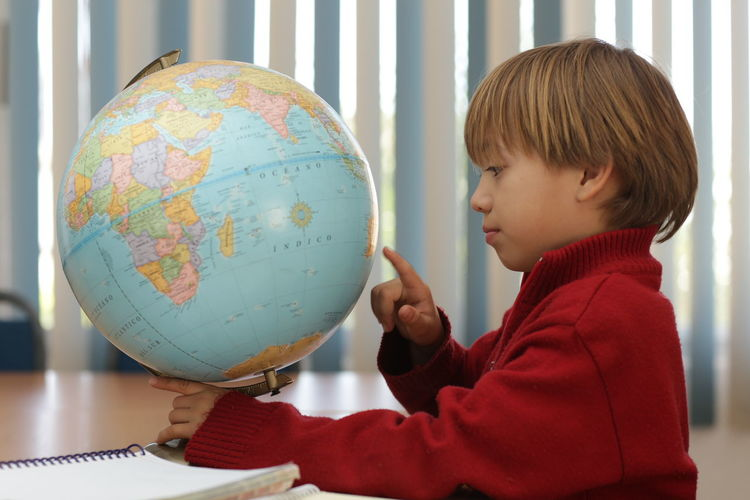 Studing Time Astronomy Boys Childhood Discovery Exploration Finger Focus On Foreground Global World Holding Learning Lifestyles Map One Person Physical Geography Planet Earth Real People Space Space Exploration World Map World Map Exploring