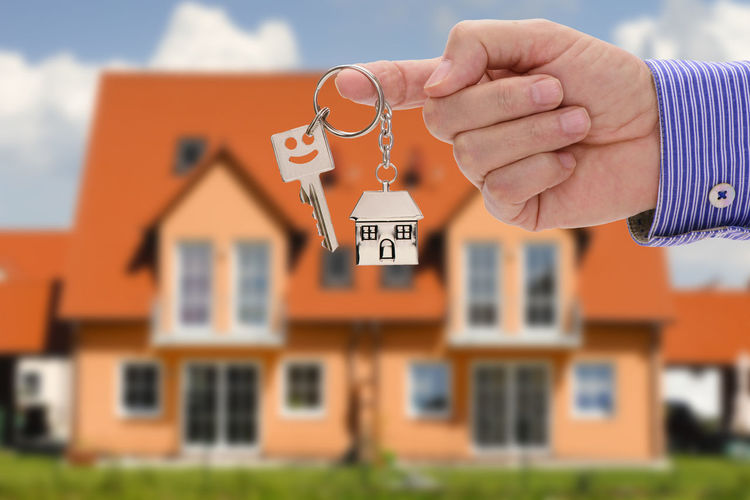Cropped Hand Of Real Estate Agent Holding Key Against House