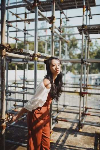 Portrait of young woman against scaffolding