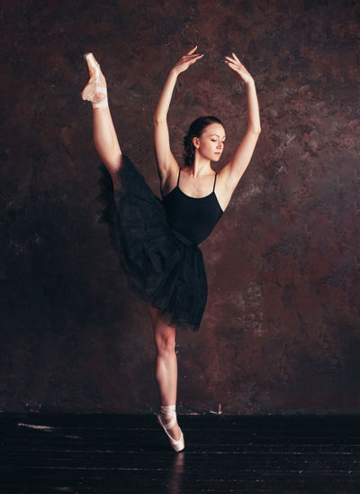 Ballet dancer ballerina in beautiful black dress tutu skirt posing in loft studio Dancing Full Length Arms Raised Human Arm One Person Young Adult Flexibility Elégance Performance Ballet Dancer Ballet Beauty Indoors  Skill  Limb Young Women Beautiful Woman Balance Body Part Human Limb Hairstyle