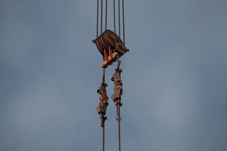 Low angle view of crane pulley against cloudy sky