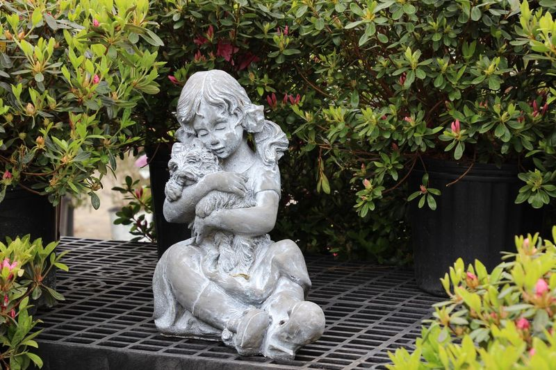 Statue Sculpture Girl And Her Puppy Plants Outdoors Daytime No People