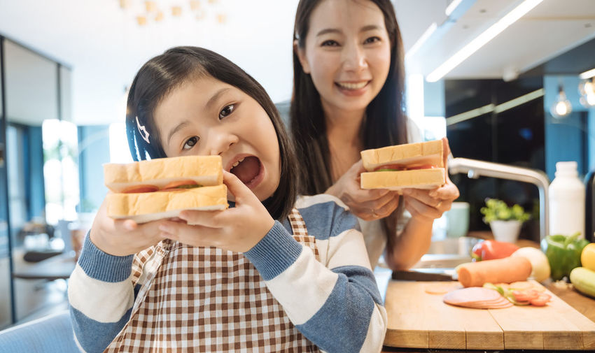 Daughter and mother preparing the sandwich and salad for breakfast in kitchen. Asian  Asian Girl Women Hapy Thai Ethnicity Japanese  Korean Taiwanese Smiling Family Love Daughter Mom Happiness Mother Girl Girls ASIA Sandwich Breakfast Baked Preparation  Food Lunch Dinner Help Helping Kitchen Cereals Milk Morning Food And Drink Two People Togetherness Lifestyles Real People Child Holding Females Focus On Foreground Portrait Childhood Adult Casual Clothing Bonding