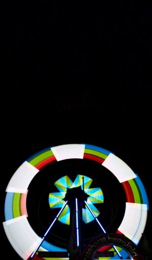 Low angle view of illuminated lighting equipment against black background