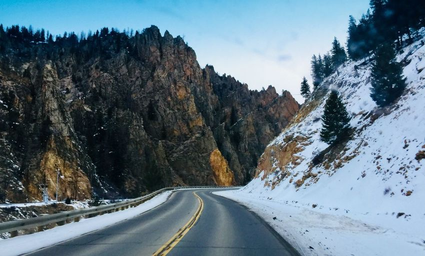 Road amidst snow covered mountains against sky