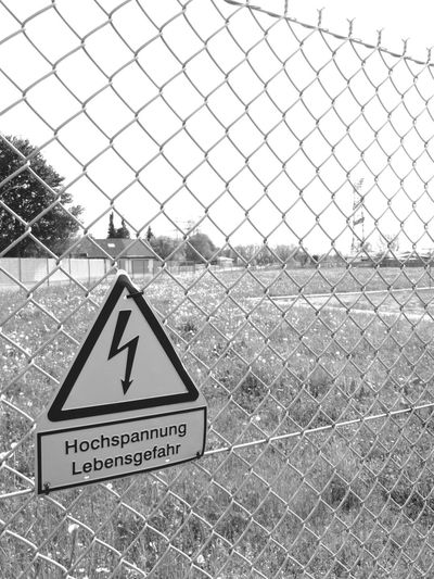 Chainlink Fence Close-up Communication Danger Day No People Outdoors Protection Safety Sky Triangle Shape Warning Warning Sign